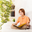 Stock Photo: Smart boy reading book on sofa