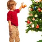 Boy decorating Christmas tree — Stock Photo