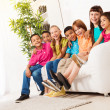 Large group of kids sitting on couch in a row — Stock Photo #32012617