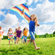 Cool girl with kite and her friends — Stock Photo