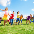 Large group of kids running in the park — Stock Photo #32013221