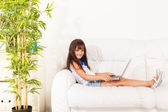 Girl with laptop on sofa in profile — Stock Photo