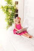 Happy little girl with sofa typing — Stock Photo