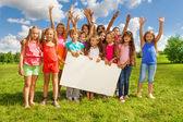 Group of kids with placecard — Stock Photo