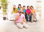 Girls singing in front of her friends — Stock Photo