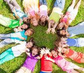Muitas crianças com mãos de levantamento na grama — Foto Stock