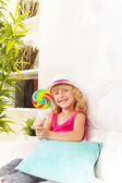 Girl with lollypop at home — Stock Photo