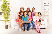Kids on the coach play with laptop — Stock Photo