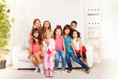 Group of happy hugging kids at home — Stock Photo