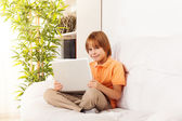 Smiling smart boy with laptop — Stock Photo
