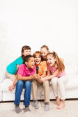 Group of kids singing on sofa — Stock Photo