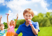 Happy boy blows horn on birthday party — Stock Photo