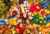 Kids lay on the autumn grass — Stock Photo