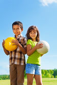 Boy and girl with balls — Stock Photo