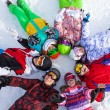 Happy friends lying in a circle on the snow — Foto Stock #44546401