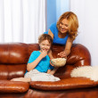 Mother with bowl of popcorn with her son — Stock Photo