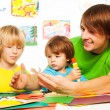 Father and his little boys cut and glue crafts from paper — Stock Photo #44546959