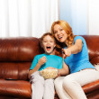 Happy mother pointing at TV and son laughing — Stock Photo