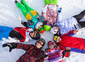 веселые друзья, лежа в круг на снегу — Стоковое фото