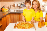Boy and happy mother slicing pizza — Stock Photo