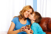 Boy is kissing his mother and giving gift to her — Stock Photo