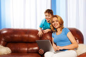Boy with mum holding laptop on the sofa — Foto Stock
