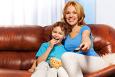 Mother with her son are watching television — Stock Photo