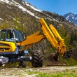 Excavator working near mountains — Stock Photo