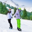 Couple standing on snowboards — Stock Photo #47609101