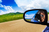 Photographer in car mirror — Stock Photo