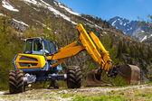 Excavator working near mountains — Foto de Stock