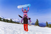 Snowboarder with woman on his shoulders — Stock Photo