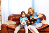 Mother and child driving  steering wheels — Stock Photo