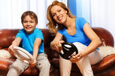 Child and mom driving steering wheels — Stock Photo