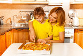 Mother and son slicing pizza — Stock Photo