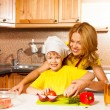 Son cuts vegetables with mother — Stock Photo