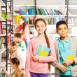 Girl and boy in library — Stok fotoğraf