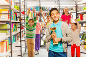Boy holds cup  in library — Photo