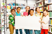 Friends holding   sheet in library — Stockfoto