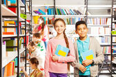 Girl and boy in library — Stock Photo