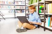 Garçon avec ordinateur portable en bibliothèque — Photo