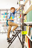 Boy climbing   in library — Stock Photo