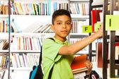 Boy  searches book — Stock Photo
