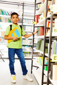 Boy with books in  library — Stockfoto