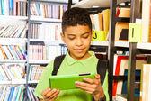 Garçon avec tablette en bibliothèque — Photo