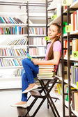 Girl sitting   in library — Stock Photo