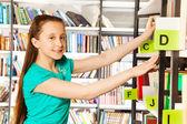 Girl   searches book — Stock Photo