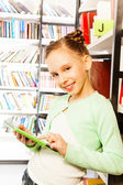 Girl plays with tablet  in library — Stock Photo