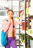 Girl   stands near bookshelf — Stock Photo