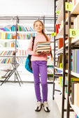Girl  with books in library — Stock Photo